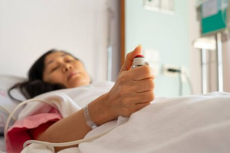 Woman patient  in hospital dress under white blanket holding red emergency call button while lying in  bed.Hand holding  nurse call button,selective focused.