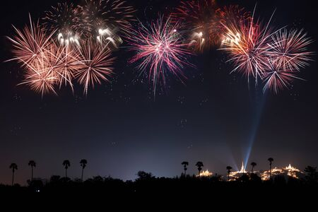 The most famous firework Pra Nakorn Kiri festival in petchaburi Thailand with palm tree silhouette in foreground and three pagodas on the hill in background.Firework display festival with copy space . 스톡 콘텐츠