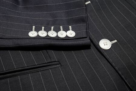 Close up detail of custom made two button jacket with pinstripe pattern fabric five sleeves buttons and front pocket , professional tailor concept.Bespoke jacket ,top view.Pay attention in every detai