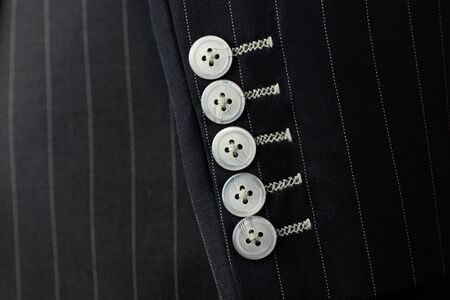 Close up detail of five sleeve  buttons and stitching for custom made jacket with pinstripe pattern fabric, professional tailor concept.Bespoke jacket selective focused on sleeve buttons,top view.Pay