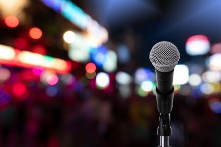 Close up of dynamic microphone setting on stand with colorful night light bokeh background ,celebration event .Microphone on stage .