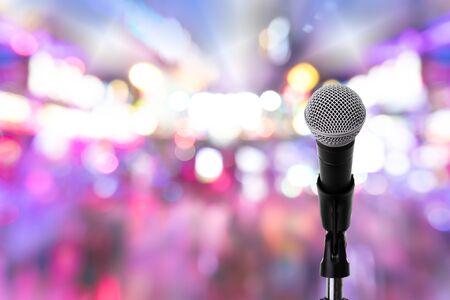 Nahaufnahme der dynamischen Mikrofoneinstellung auf dem Ständer mit buntem hellem Bokeh-Hintergrund, Feierereignis. Mikrofon auf der Bühne.