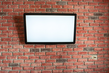 On the red interior brick wall is a white screen TV