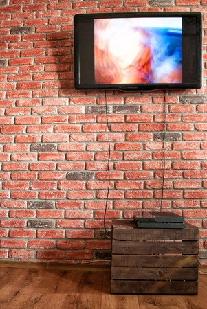 Game console on a vegetable box against a brick wall with a TV