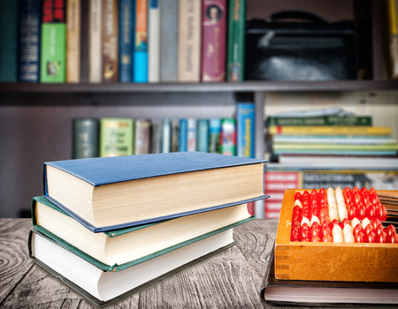 Books stacked vertically and bills with a notebook on the desk against the backdrop of the bookshelf. Education concept.