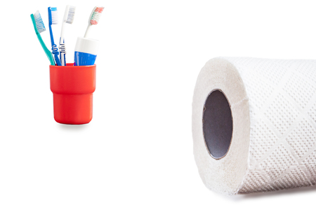 Roll of paper towels and toothbrushes in a red container isolated on white