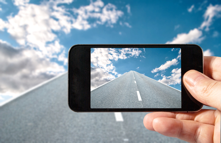 The road goes to the sky on the monitor of a modern phone