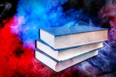 books stacked on top of each other and a colorful background Stok Fotoğraf