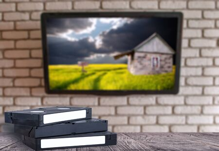 VHS video tapes on the desk brick wall with a TV Stok Fotoğraf