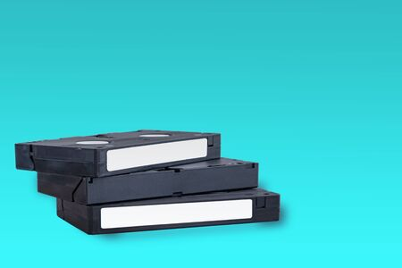 VHS videotapes on a blue background stacked vertically on each other
