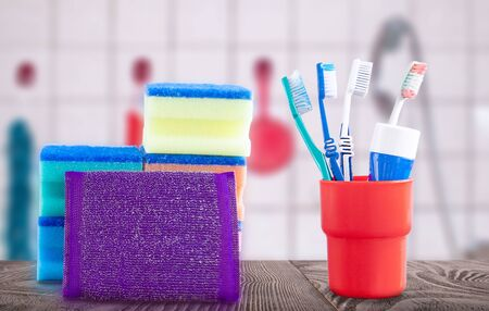 Red container with toothbrushes and toothpaste on a wooden surface and washcloth