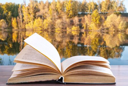 open book on nature background with lake