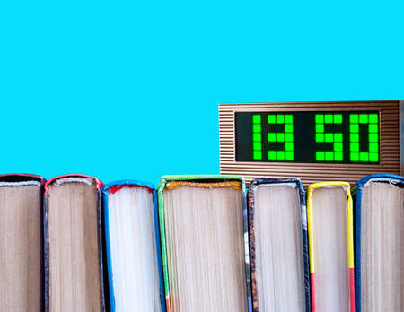 row of books and electronic clock on a blue background
