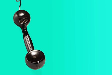 black handset with wire hang against a blue wallpaper texture.