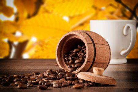 coffee beans and coffee cup on a wooden surface