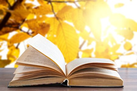 Open book on a wooden surface on a background of autumn trees and yellow leaves