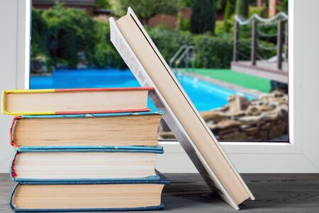 a stack of books near a window and a pool in the blurred background