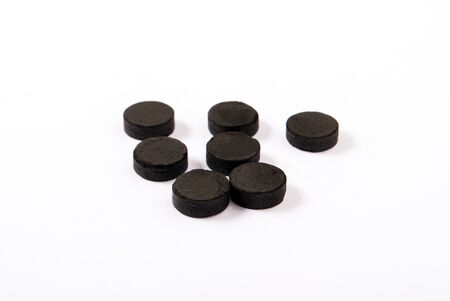 Activated carbon in tablets isolated on white.