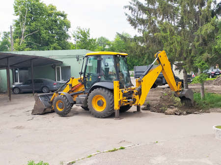 Wheeled excavator with metal bucket for digging trenches and pits