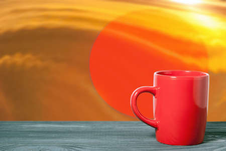 Red mug on a table surface against a background of a red circle. Drinks concept.