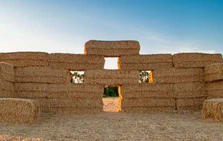 dry stack of straw stacked on top of each other in the form of a castle at sunset
