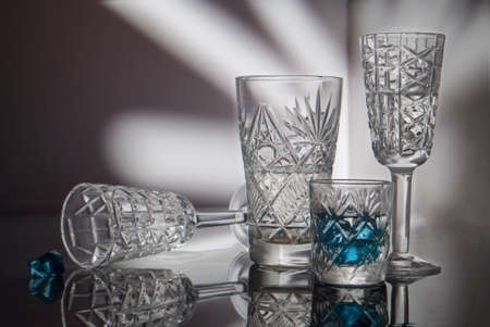 Crystal glasses on a mirror surface and a beautiful background painted with light 版權商用圖片