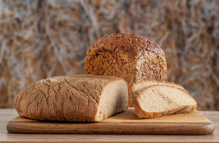 wheat and rye bread on blurred straw background