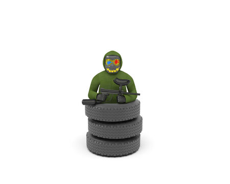 Paintballer in protective mask with spots of paint stands in a pile of tires