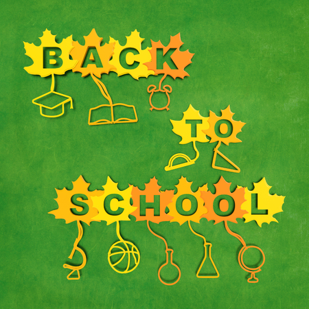 academic symbol: Back to school creative concept. Yellow and orange maple leaves with text and with stalks in the form of school supplies on blackboard background as symbol of beginning of the school academic year