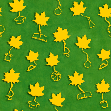 School season seamless background. Yellow maple leaves with stalks in the form of school supplies on green blackboard background as symbol of beginning of the school (academic) year