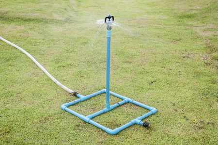 water garden: Garden sprinkler on a sunny summer day during watering the green lawn in garden