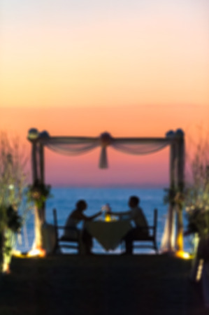 love image: young couple with a romantic dinner with candles on the sea sand beach-blurred image