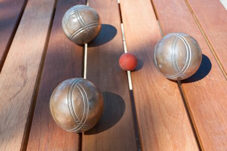 bocce: Metallic petanque balls and a small red jack on wood table Stock Photo