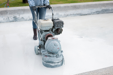 grinding the cement floor pool machine and worker photo