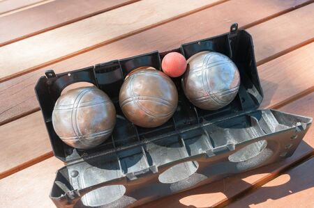 bocce ball: Metallic petanque balls and a small red jack on wood  table