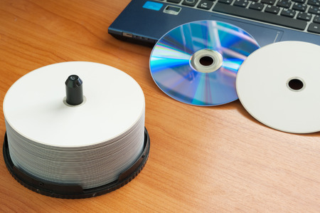 optical disk: Office desk with laptop computer, and disc dvd Stock Photo