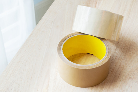sticky tape: two roll of brown sticky tape on wood panel background Stock Photo