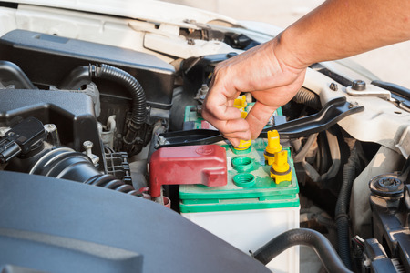 distilled water: Hands of mechanic working in auto repair shop Add distilled water in battery