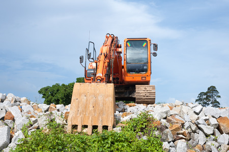 Orange backhoe parked on the rocks