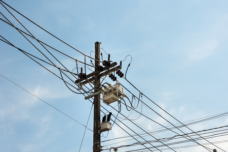 Power lines and insulators with blue sky Stock Photo