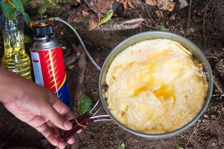 Fried eggs on a portable gas burner in the tourist camp. Stock Photo