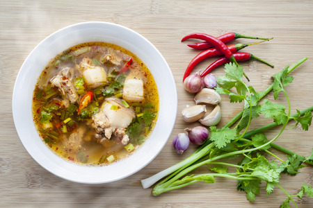 Hot and spicy soup pork on wooden plate with top view Imagens