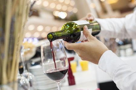 Czerwonego wina dolewanie w wina szkło z bokeh na tle