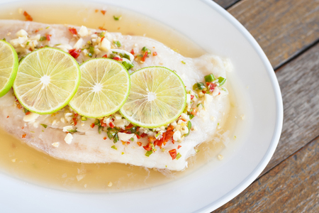 Steamed fish in lime on wooden table brown with thai style Stock Photo