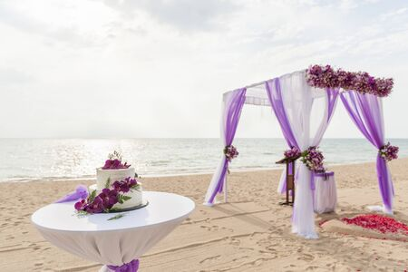 Wedding cake on the beach decorated with purple orchid flower Standard-Bild