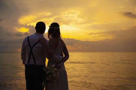 Feliz pareja de novios románticos enamorados y mirar el horizonte con puesta de sol