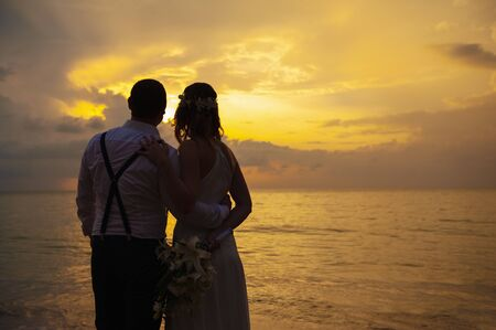 gelukkig romantisch bruidspaar verliefd en kijk naar de horizon met zonsondergang