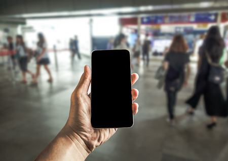 Close up of hands using cell phone at a station platform, many people background