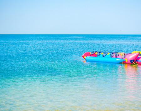 Calm Sea Ocean With Banana Boat And Blue Clear Sky on sandy beach Background. Stock Photo