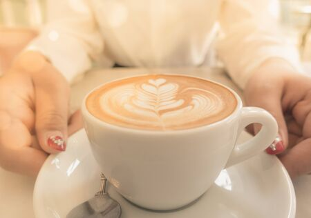 Closeup of woman holding warm latte hot cup of coffee
